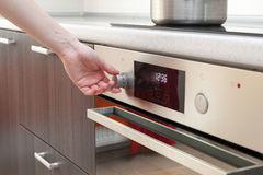 Schließen Sie oben von der Frauenhandeinstellung, die Modus auf Ofen kocht Stockbilder