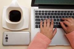 Schließen Sie oben von der Geschäftsfrauhand, die im Büro, im Laptop, in der Schale coffe und im smarphone im Bild arbeitet Gesch Stockbild