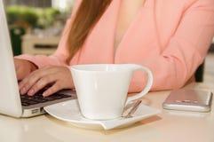 Schließen Sie oben von der Geschäftsfrauhand, die mit einer Hand ein Schale coffe bearbeitet und hält Die goldene Taste oder Erre Stockfoto