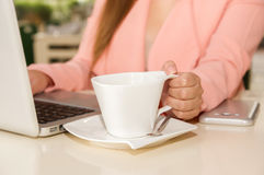 Schließen Sie oben von der Geschäftsfrauhand, die mit einer Hand ein Schale coffe bearbeitet und hält Die goldene Taste oder Erre Lizenzfreie Stockbilder