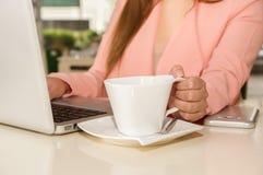 Schließen Sie oben von der Geschäftsfrauhand, die mit einer Hand ein Schale coffe bearbeitet und hält Die goldene Taste oder Erre Lizenzfreies Stockbild