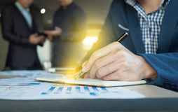 Schließen Sie oben von der Geschäftsmannhandschrift auf Notizbuchpapier mit Bus Lizenzfreie Stockfotos