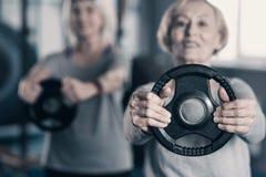 Schließen Sie oben von der Gewichtsdiskette in den Händen älterer Dame lizenzfreie stockfotografie