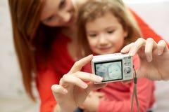 Schließen Sie oben von der glücklichen Mutter und von der Tochter mit Kamera Stockfotografie