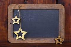 Schließen Sie oben von der hölzernen Tafel mit Sternen für ein Weihnachten-greetin Stockfotos