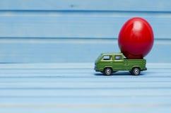 Schließen Sie oben von der Hühnerei auf Spielzeugauto auf einem blauen hölzernen Hintergrund Lizenzfreie Stockfotos