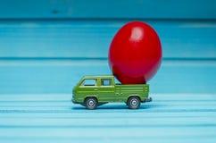 Schließen Sie oben von der Hühnerei auf Spielzeugauto auf einem blauen hölzernen Hintergrund Abstraktes Retro- Konzept Stockfoto