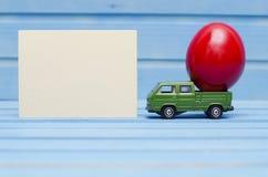 Schließen Sie oben von der Hühnerei auf Spielzeugauto auf einem blauen hölzernen Hintergrund mit leerer Karte Abstraktes Retro- K Lizenzfreie Stockfotografie