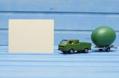 Schließen Sie oben von der Hühnerei auf Spielzeugauto auf einem blauen hölzernen Hintergrund mit leerer Karte Abstraktes Retro- K Stockfotografie