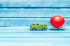 Schließen Sie oben von der Hühnerei auf Spielzeugauto mit einem Anhänger auf einem blauen hölzernen Hintergrund Stockfotos