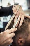 Schließen Sie oben von der Hand des Kosmetikers, die dem männlichen Kunden einen Haarschnitt am Wohnzimmer gibt Lizenzfreies Stockbild
