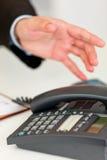 Schließen Sie oben von der Hand, die auf Bürotelefon sich ausdehnt Stockbilder