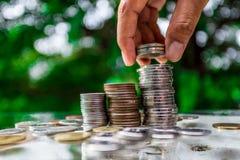 Schließen Sie oben von der Hand, die Goldmünzen mit grünem bokeh Hintergrund, Geschäfts-Finanzierung stapelt und Geldkonzept, spa Stockfotografie