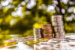 Schließen Sie oben von der Hand, die Goldmünzen mit grünem bokeh Hintergrund, Geschäfts-Finanzierung stapelt und Geldkonzept, spa Lizenzfreies Stockbild