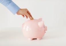 Schließen Sie oben von der Hand, die Münze zum Sparschwein setzt Stockfoto