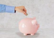 Schließen Sie oben von der Hand, die Münze zum Sparschwein setzt Lizenzfreie Stockfotos