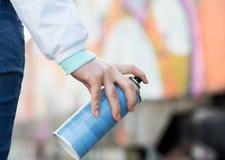 Schließen Sie oben von der Hand, die Sprühfarbe und Graffiti hält Stockbild