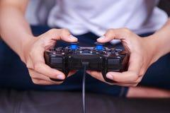 Schließen Sie oben von der Hand, die Videospiel mit einem Steuerknüppel spielt Lizenzfreie Stockfotografie