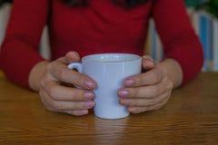 Schließen Sie oben von der Hand, die weiße Schale mit heißem Kaffee hält stockfoto