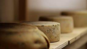 Schließen Sie oben von der Hand einer Frau, die Käse von einem Regal im Lagerraum nimmt