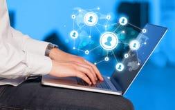 Schließen Sie oben von der Hand mit Laptop und Social Media-Ikonen Lizenzfreies Stockbild