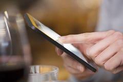 Schließen Sie oben von der Handfrau, die ihren Handy im Restaurant, coff verwendet Lizenzfreies Stockfoto
