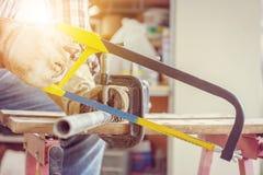 Schließen Sie oben von der Handwerkerarbeitskraft, die ein Stahlrohr, Technikerkonzept sägt stockbild
