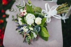 Schließen Sie oben von der Heirat des Brautblumenstraußes mit Rosen auf dem Stuhl stockfoto