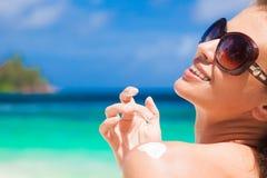 Schließen Sie oben von der jungen Frau in der Sonnenbrille, die Sonnencreme auf Schulter setzt Lizenzfreies Stockfoto