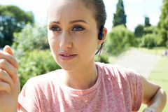 Schließen Sie oben von der jungen Frau, die in den Park läuft, der Musik hört lizenzfreie stockfotos