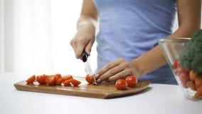 Schließen Sie oben von der jungen Frau, die zu Hause Tomaten hackt stock footage
