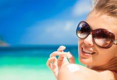 Schließen Sie oben von der jungen Frau in der Sonnenbrille, die Sonnencreme auf Schulter setzt Stockfotografie