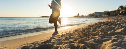 Schließen Sie oben von der jungen gesunden Lebensstileignungsfrau, die am Sonnenaufgangstrand läuft Lizenzfreie Stockfotografie