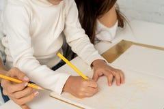 Schließen Sie oben von der jungen glücklichen Mutter und von der kleinen Sohnzeichnung mit farbigen Bleistiften lizenzfreies stockbild