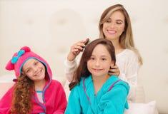 Schließen Sie oben von der jungen Mutter, die das Haar ihres wenig daugher brussing ist, das ein blaues bathtowel während ihr and stockfotos