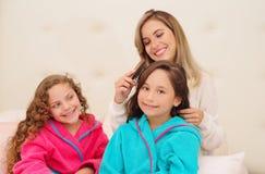 Schließen Sie oben von der jungen Mutter, die das Haar ihres wenig daugher brussing ist, das ein blaues bathtowel während ihr and stockfoto