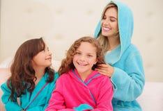 Schließen Sie oben von der jungen Mutter, die das Haar ihres wenig daugher brussing ist, das ein blaues bathtowel während ihr and lizenzfreies stockbild