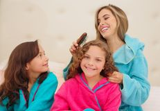 Schließen Sie oben von der jungen Mutter, die das Haar ihres wenig daugher brussing ist, das ein blaues bathtowel während ihr and lizenzfreie stockbilder
