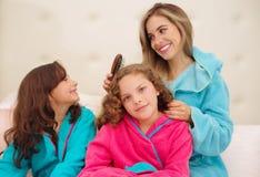 Schließen Sie oben von der jungen Mutter, die das Haar ihres wenig daugher brussing ist, das ein blaues bathtowel während ihr and lizenzfreies stockfoto
