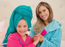 Schließen Sie oben von der jungen Mutter, die eine Massage zu ihrem kleinen gelockten Mädchen in einem Damennachtausgangsbadekuro lizenzfreie stockfotos