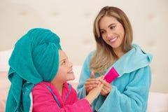 Schließen Sie oben von der jungen Mutter, die eine Massage zu ihrem kleinen gelockten Mädchen in einem Damennachtausgangsbadekuro stockfotografie