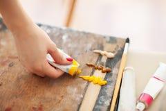 Schließen Sie oben von der Künstler ` s Hand, die von einer Rohrfarbe auf blassem zusammengedrückt wird stockfotos