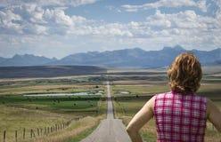 Schließen Sie oben von der kaukasischen Frau, die in Richtung zu einem langen Schotterweg im Sommer gegenüberstellt Stockbilder