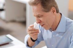 Schließen Sie oben von der kranken männlichen Person, die seine Lippen bedrängt Lizenzfreies Stockbild