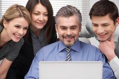 Schließen Sie oben von der lächelnden Gruppe von Personen, die Laptop betrachtet. Lizenzfreie Stockfotos