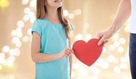 Schließen Sie oben von der Mädchen- und Vaterhand, die rotes Herz hält stockfoto