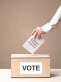 Schließen Sie oben von der männlichen Hand, die Abstimmung in eine Wahlurne setzt Lizenzfreies Stockfoto