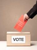 Schließen Sie oben von der männlichen Hand, die Abstimmung in eine Wahlurne setzt Stockbilder