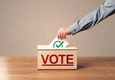 Schließen Sie oben von der männlichen Hand, die Abstimmung in eine Wahlurne setzt Stockfotos