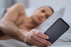 Schließen Sie oben von der männlichen Hand diesen zeigenden Smartphone Stockfotografie